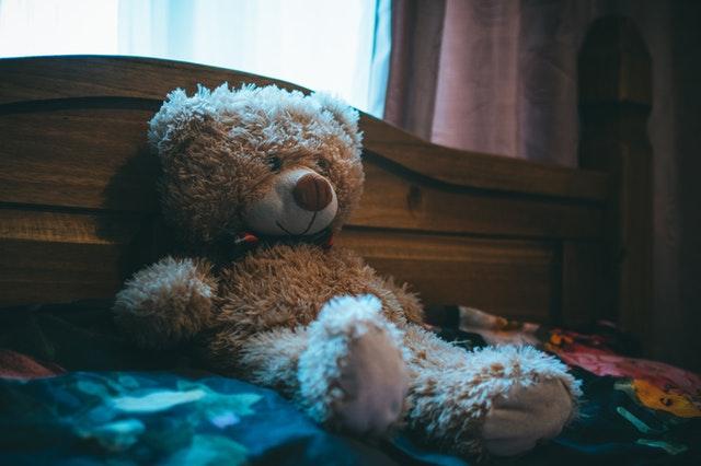 plyšový medvěd na dřevěné posteli